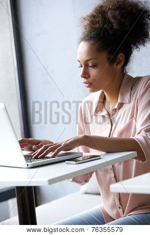 Young African American Woman Typing On Laptop