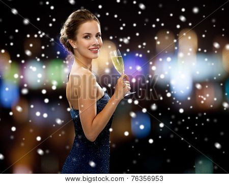 party, drinks, holidays, christmas and people concept - smiling woman in evening dress with glass of sparkling wine over night lights and snow background