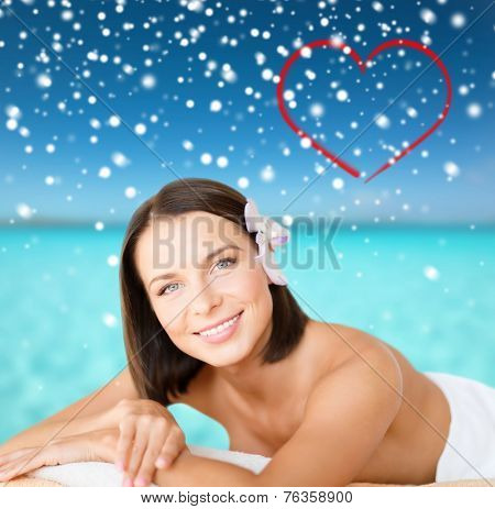 beauty, health, people and spa concept - beautiful young woman in spa with red heart shape over blue sky, sea and snowflakes background