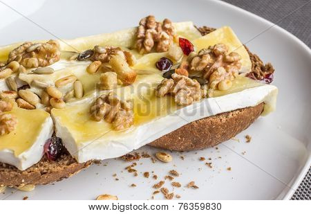 Melted Brie With Honey And Walnuts On Dark Bread