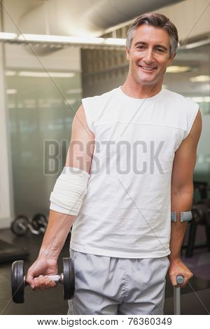 Injured man holding dumbbell in the weights room at the gym