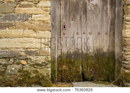Entire old wooden door with moss and lock, sone wall