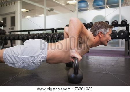 Fit man using kettlebells in his workout at the gym
