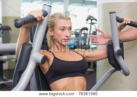 Portrait of a fit young woman using fitness machine at the gym