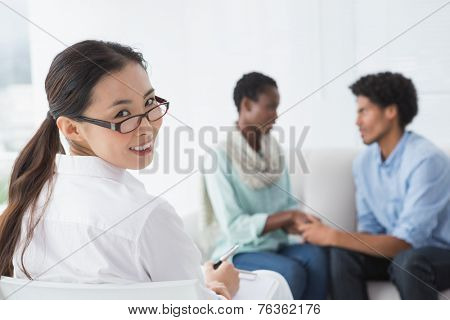 Reconciled couple smiling at each other in therapists office