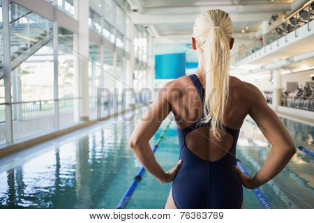 Rear view of a fit female swimmer standing by the pool at leisure center