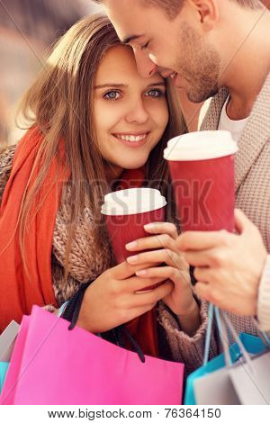 A picture of a joyful couple shopping in the mall with coffee