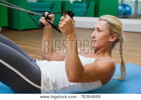 Side view of a sporty young woman using resistance band in fitness studio