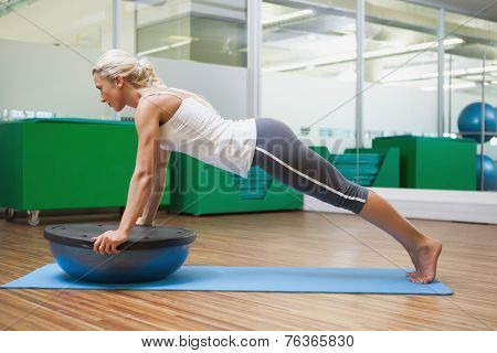 Full length of a young woman doing fitness exercise in fitness studio