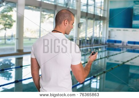 Swimming coach looking at his stopwatch by the pool at the leisure center