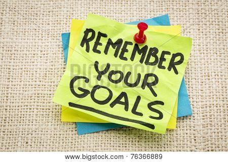 remember your goals advice on a green sticky note against burlap canvas