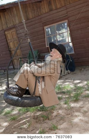 Senior Man Swinging On A Tire Swing