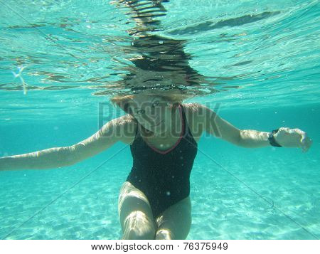 Female With Eyes Open Underwater In Ocean