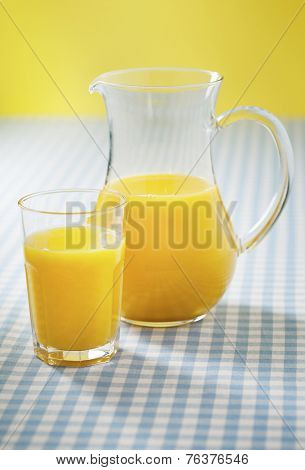 A glass and pitcher with orange juice. Short depth-of-field.