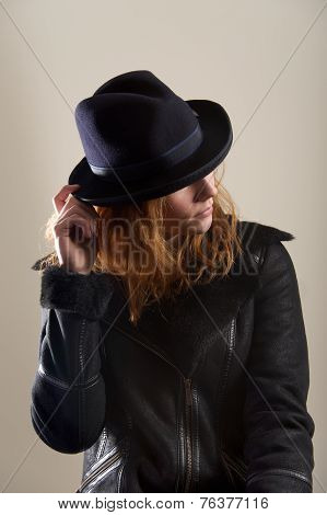 Redhead Touching Brim Of Blue Felt Hat