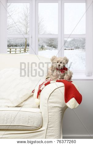 Little teddy bear sitting on a Christmas stocking on the arm of a chair