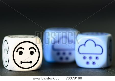 Concept Of Sad Snow / Winter Weather - Emoticon And Weather Dice On Black Background