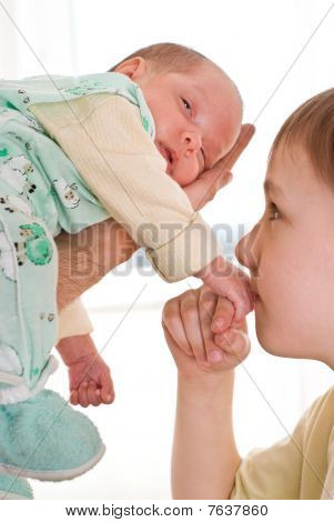Boy Kissing A Newborn Sister's Hand
