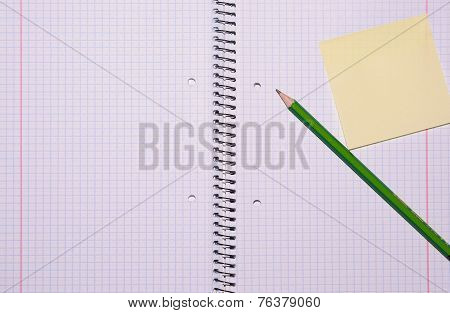 Open Exercise Book With Sticky Card And Pencil Seen From Top