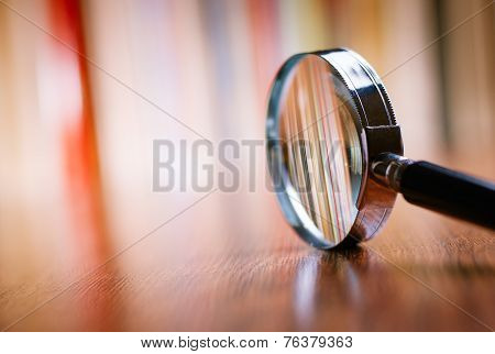 Close Up Magnifying Glass Leaning On Wooden Table