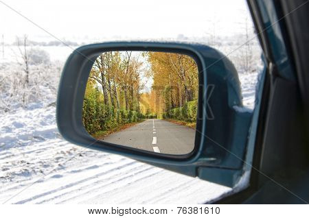 rural road in the autumn with yellow colored trees reflected in car mirror