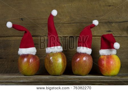 Decoration: Funny christmas greeting card with four red santa hats on apples with wooden background.
