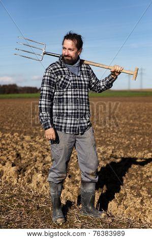 Portrait Of A European Farmer With A Pitchfork