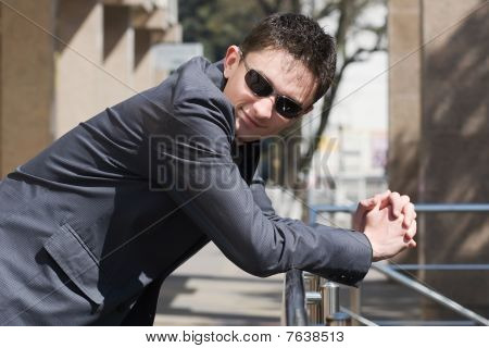 Young Adult European Businessman In Jacket Leans On Handrails