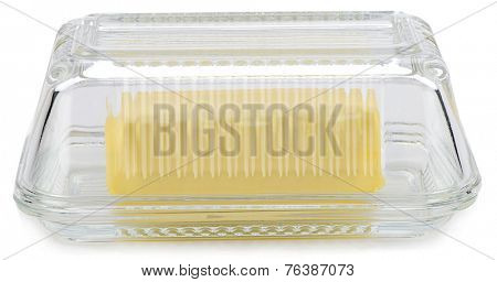 Piece of butter in glass butter dish isolated on white background.