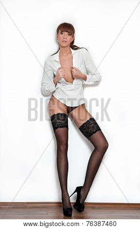 Attractive red hair model with black stocking standing on gray wall