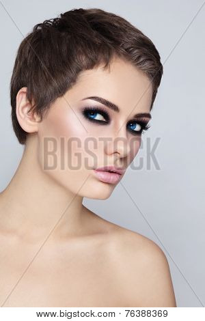 Portrait of young beautiful woman with stylish haircut and smokey eyes