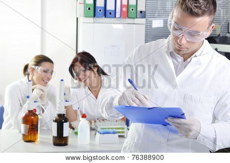 Attractive Young Phd Student Scientist Writing A Note In Laboratory