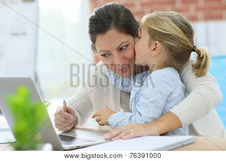 Little girl giving kiss to her mom while working from home