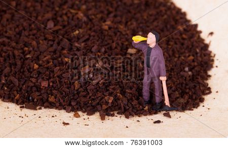 Miniature Worker Working On Grinded Coffee