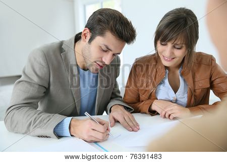 Young couple in real estate agency signing property agreement