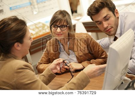 Couple in optical center with optician ordering eyeglasses