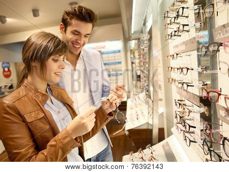 Young couple in optical shop trying eyeglasses