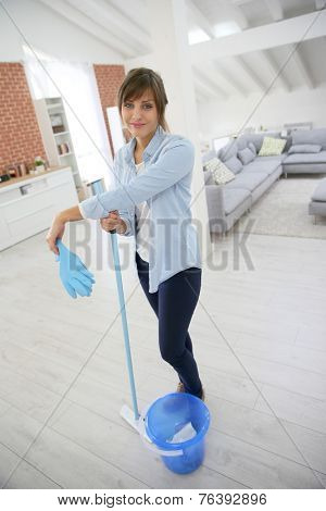 Young housekeeper standing with mopping equipment