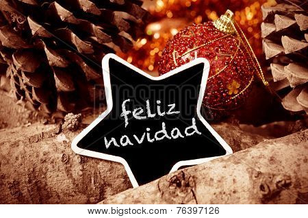 the text feliz navidad, merry christmas written in spanish in a star-shaped blackboard, and some christmas ornaments, and pinecones and a pile of logs in the background