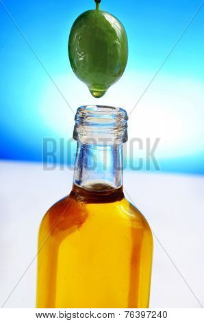 closeup of an olive bleeding oil to a bottle