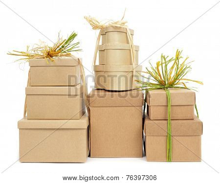 some gift boxes tied with natural raffia of different colors on a white background