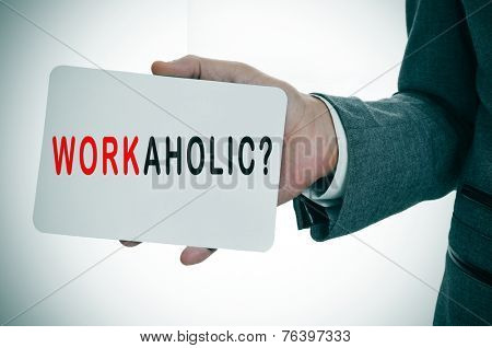 a young businessman showing a signboard with the word workaholic written in it