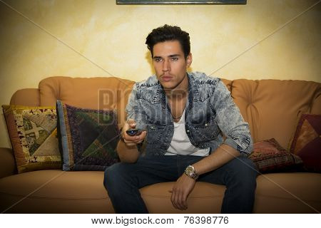 Young Man Sitting Watching Tv With Remote Control