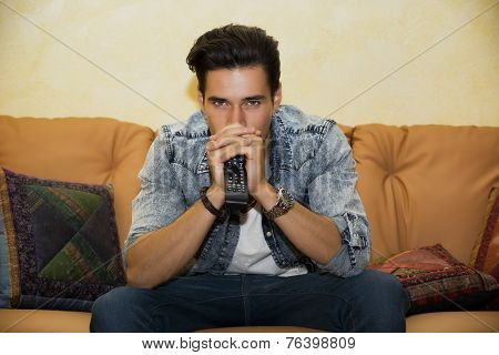 Young Man Sitting Watching Television Changing The Channel