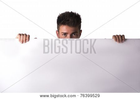 Attractive Young Man Or Teenager Peeking Over Blank White Display