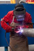 pic of pipe-welding  - welder in factory with protective equipment welding metal pipes