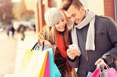 picture of couples  - A picture of a couple shopping with smartphone in the city - JPG