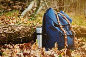pic of thermos  - Thermos and backpack outdoors on autumn nature hiking theme - JPG