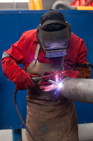 pic of pipe-welding  - welder in factory with protective equipment welding metal pipes  - JPG