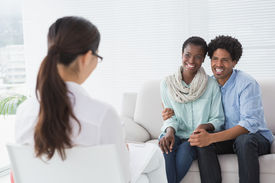 picture of therapist  - Reconciled couple smiling at their therapist in therapists office - JPG